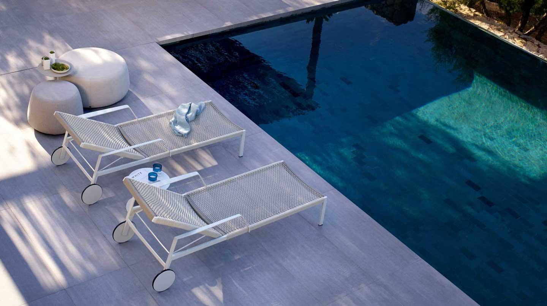lettini da sole e pouf a bordo piscina