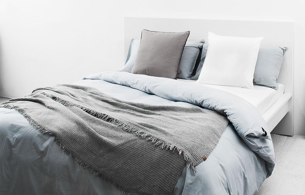 letto con copripiumino e coperta in lana dai colori neutri